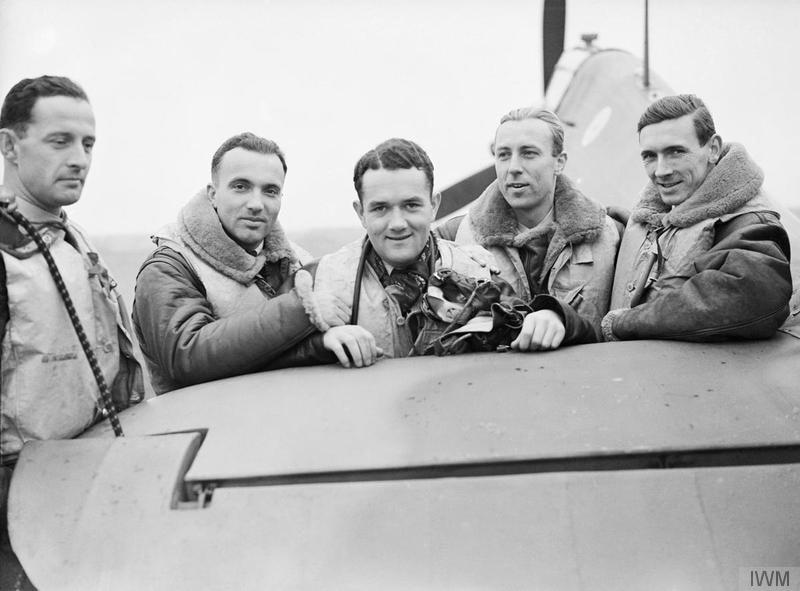 Des pilotes du 303e Escadron polonais de la Royal Air Force posent à côté d'un de leur Hawker Hurricane à la base Leconfield de la RAF, dans le Yorkshire, le 24 octobre 1940, tard dans la bataille d'Angleterre. Dans la photo, on voit le sous lieutenant d'aviation Miroslaw Feric (à gauche), le lieutenant d'aviation Bogdan Grzeszczak, le sous lieutenant d'aviation Jan Zumbach, le lieutenant d'aviation Zdzislaw Henneberg et le capitaine d'aviation canadien John Kent, qui commandait l'escadrille « A » durant cette période. PHOTO : © Imperial War Museum (CH 1533)