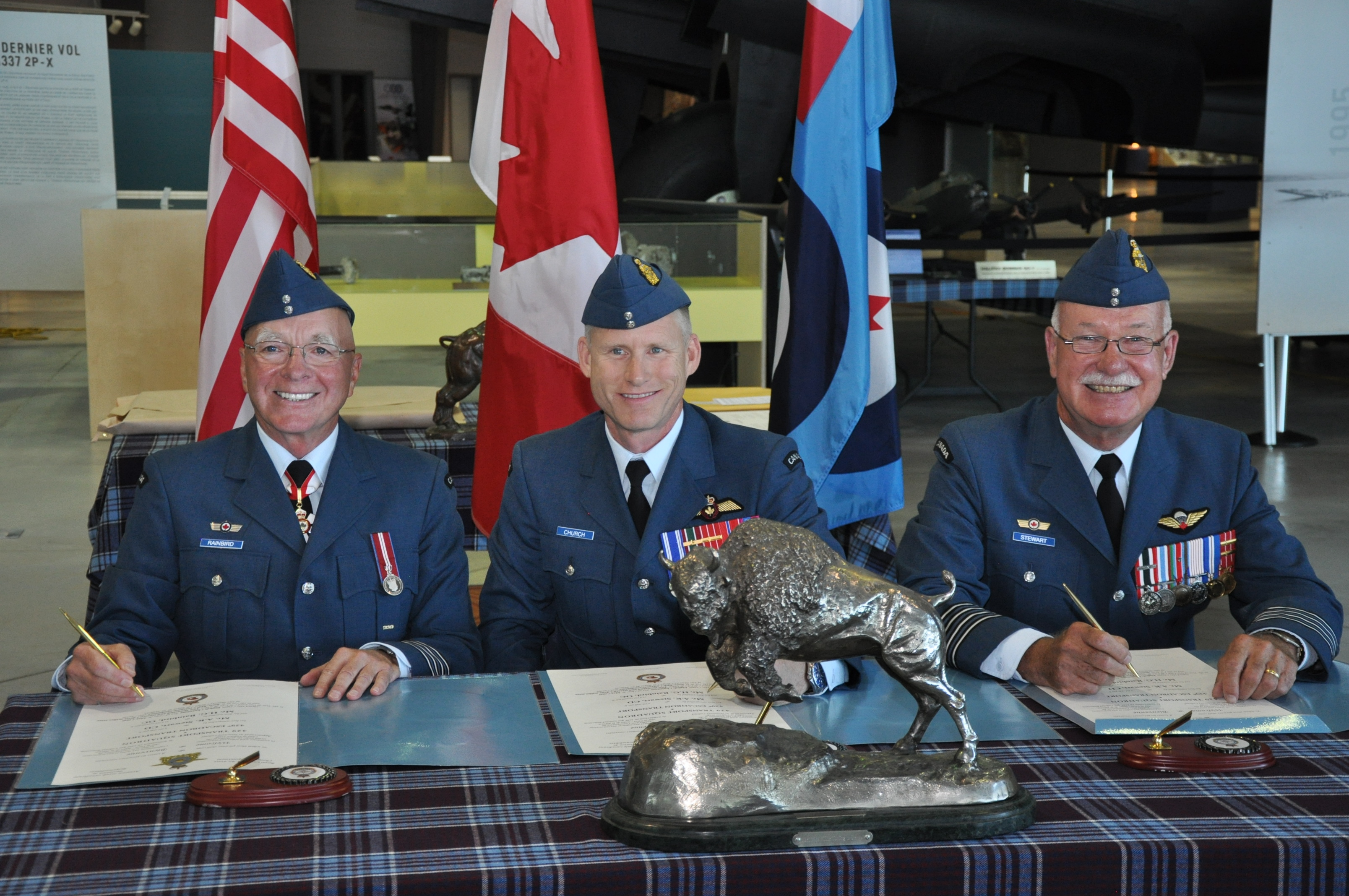 Three men in Royal Canadian Air Force dress uniforms sit behind a table covered in an RCAF tartan cloth.