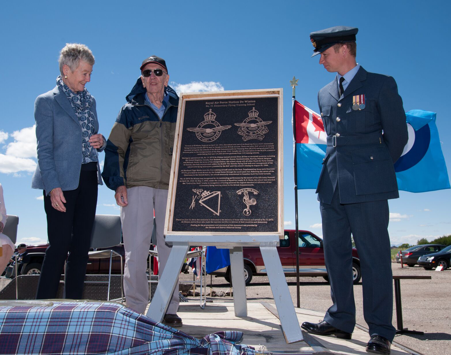 A woman, an elderly man and a young man in a Royal Air Force uniform stand beside a large bronze plaque on an easel.
