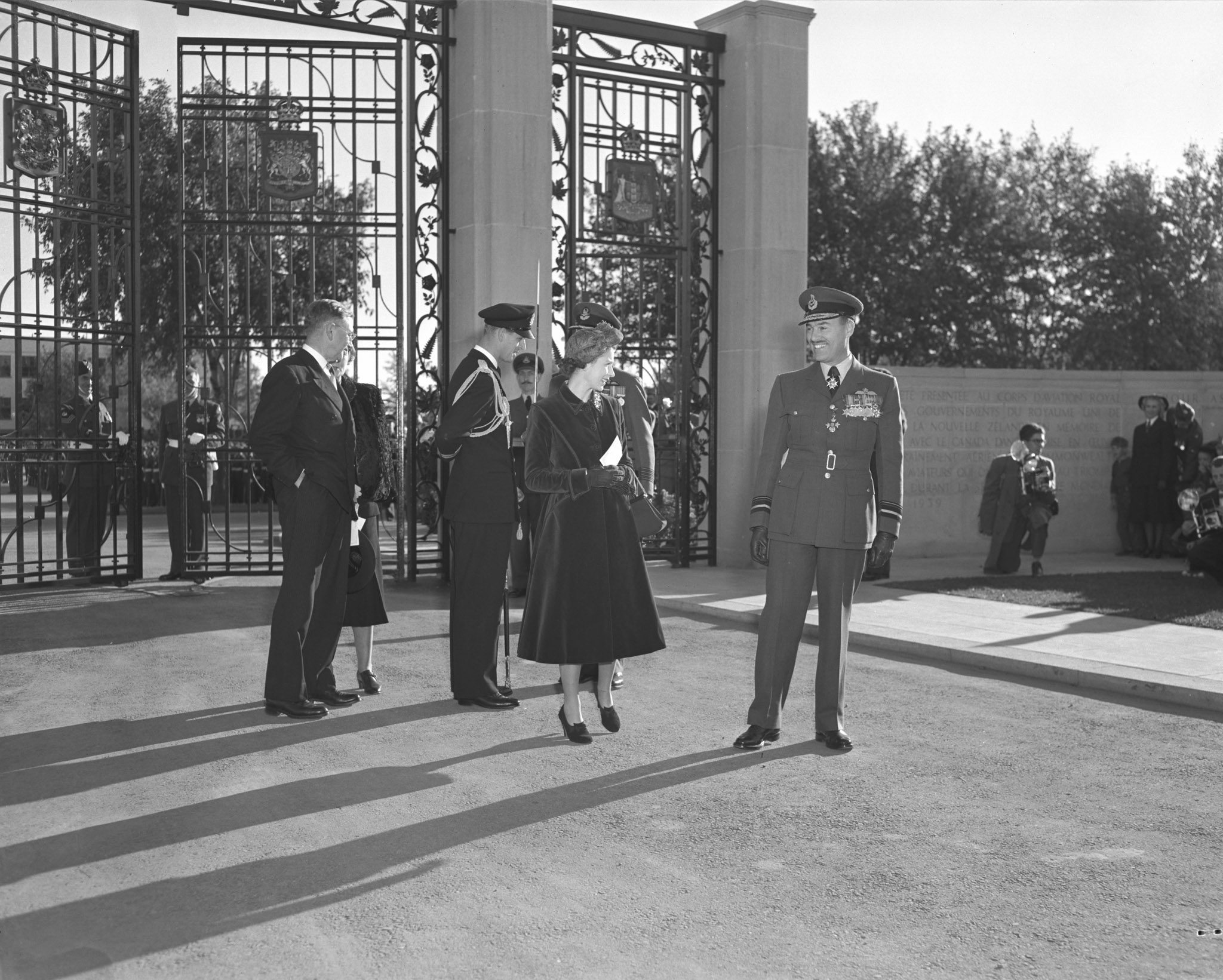 Le vice-maréchal de l'Air Charles Roy Slemon, commandant de l'aviation du Commandement de l'instruction, s'entretient avec la princesse Elizabeth à l'arrivée du couple royal à Trenton. Le commandant de défilé, le colonel d'aviation G.P. Dunlop (partiellement caché) accompagne le duc d'Édimbourg, sous les regards du ministre de la Défense, Brooke Claxton, et de son épouse, Helen Claxton. PHOTO: Archives du MDN, PL-52814