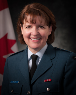 A photo of a woman in a dress blue Air Force uniform looking at the camera.