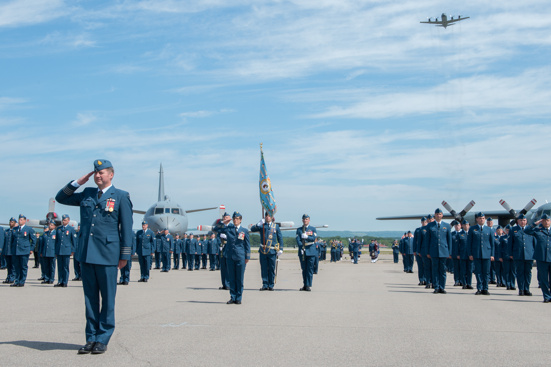 Newly-appointed 14 Wing Greenwood, Nova Scotia, commander Colonel Mike Adamson leads the July 20, 2017, change of command parade through the advance in review order, as one of the wing's signature CP-140 Auroras flies overhead. PHOTO: Corporal Dan Salisbury, GD04-2017-0453-034