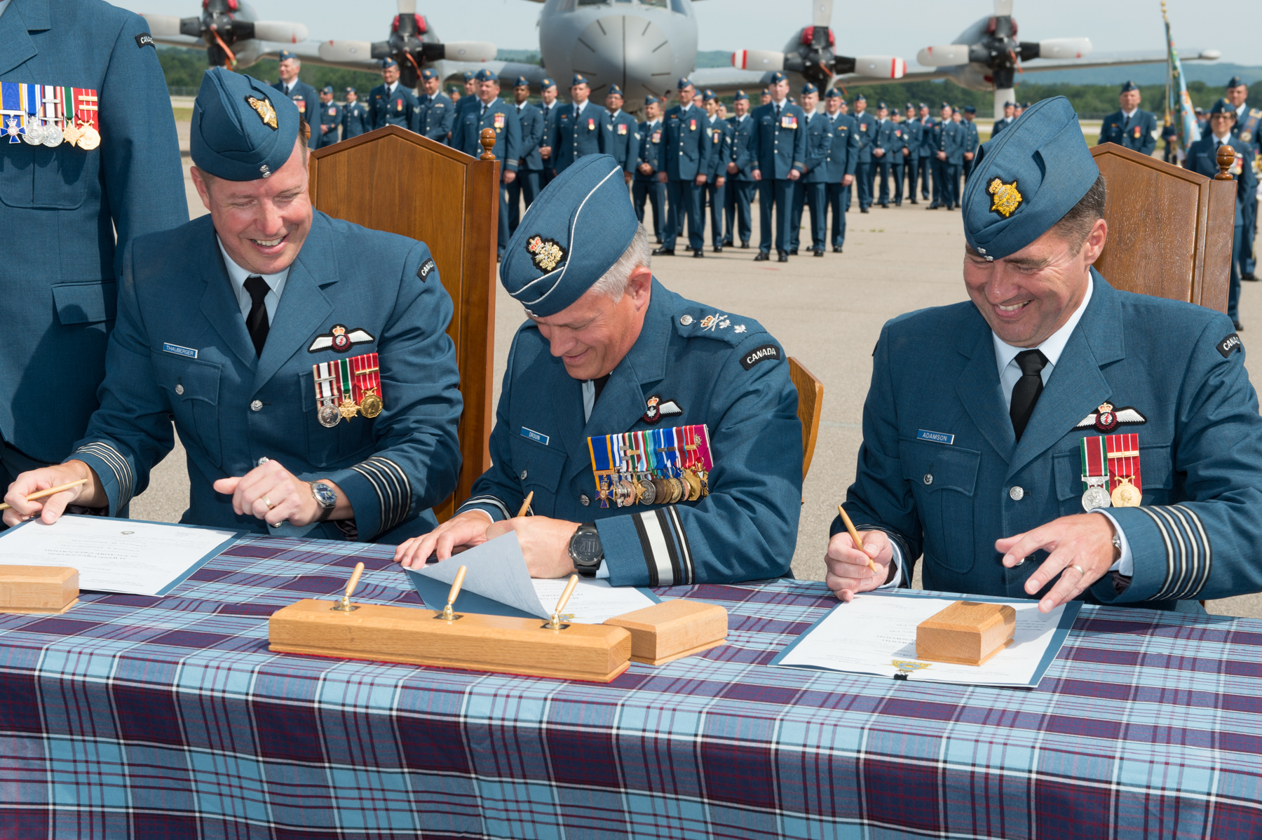 Sitting outdoors at a table covered with a tartan cloth, three men in blue military uniforms hold pens and prepare to sign one document each. Behind them stand ranks of people in blue military uniforms.