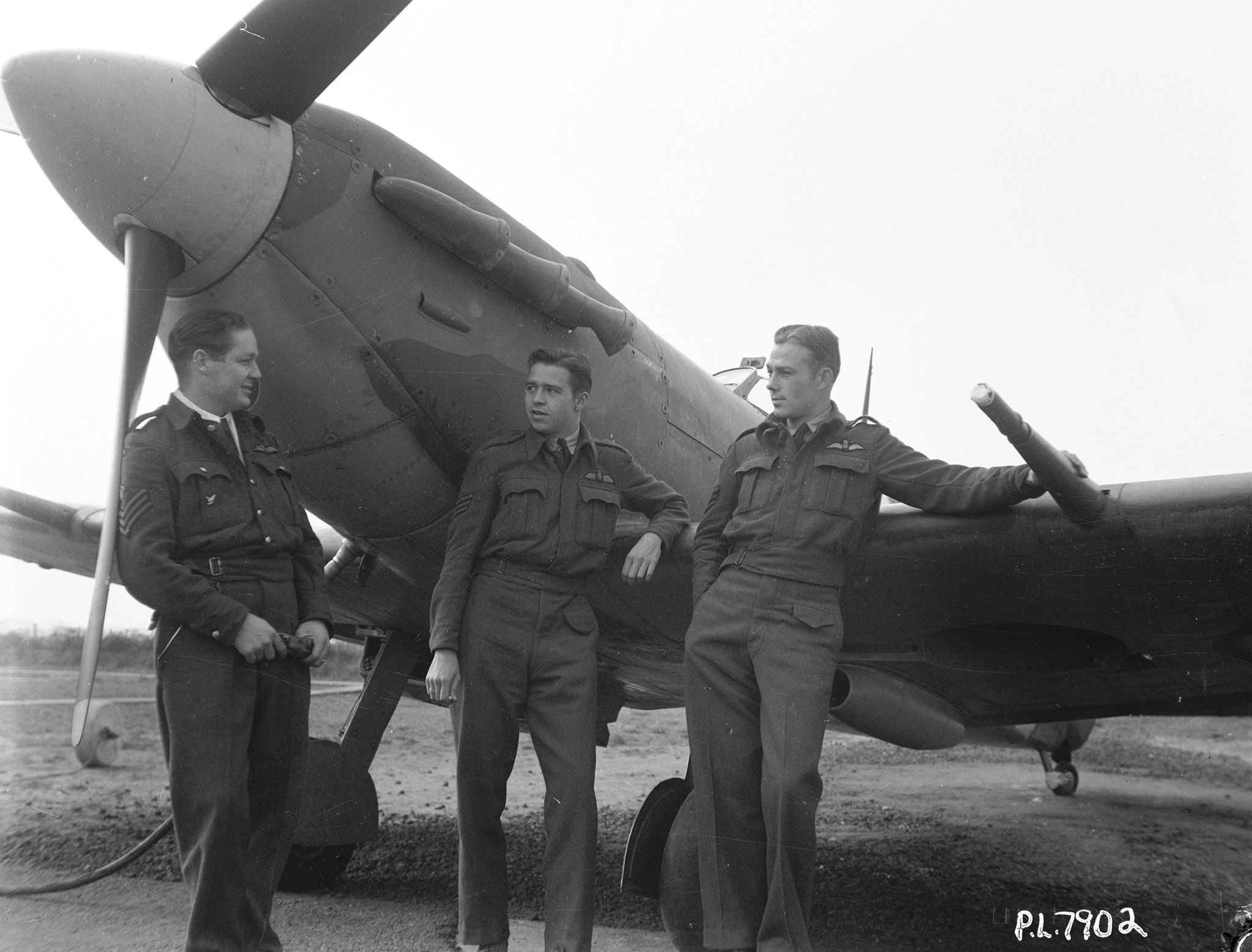 "American members of 411 Squadron, photographed in June 1942. The original caption to this photo reads: ""There were plenty of U.S. lads who anticipated their own country's entry into the war by joining the Royal Canadian Air Force. Here are three who are typical. All are now with a Canadian Spitfire squadron. They are, from left to right, Flight Sergeant Tex Linton, of Herrin, Illinois; Sergeant R. J. Messenger, of Erie, Pennsylvania, and Sergeant G. P. Fraser, of Memphis, Tennessee."" PHOTO: DND Archives, PL-7902"