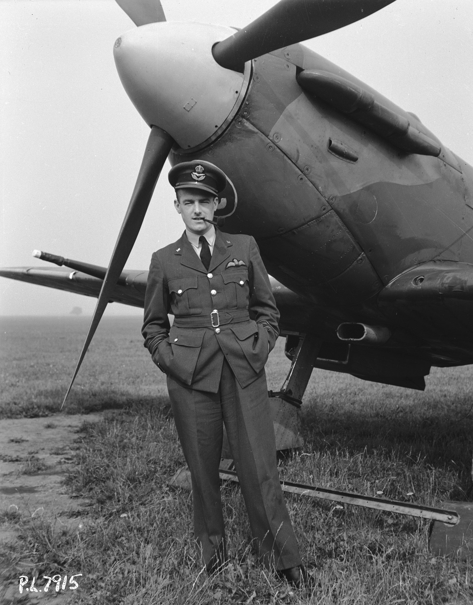 A black and white photo of a man wearing an air force dress uniform and hat, with his hands in his pockets and smoking a pipe, standing in front of an old propeller-driven aircraft.