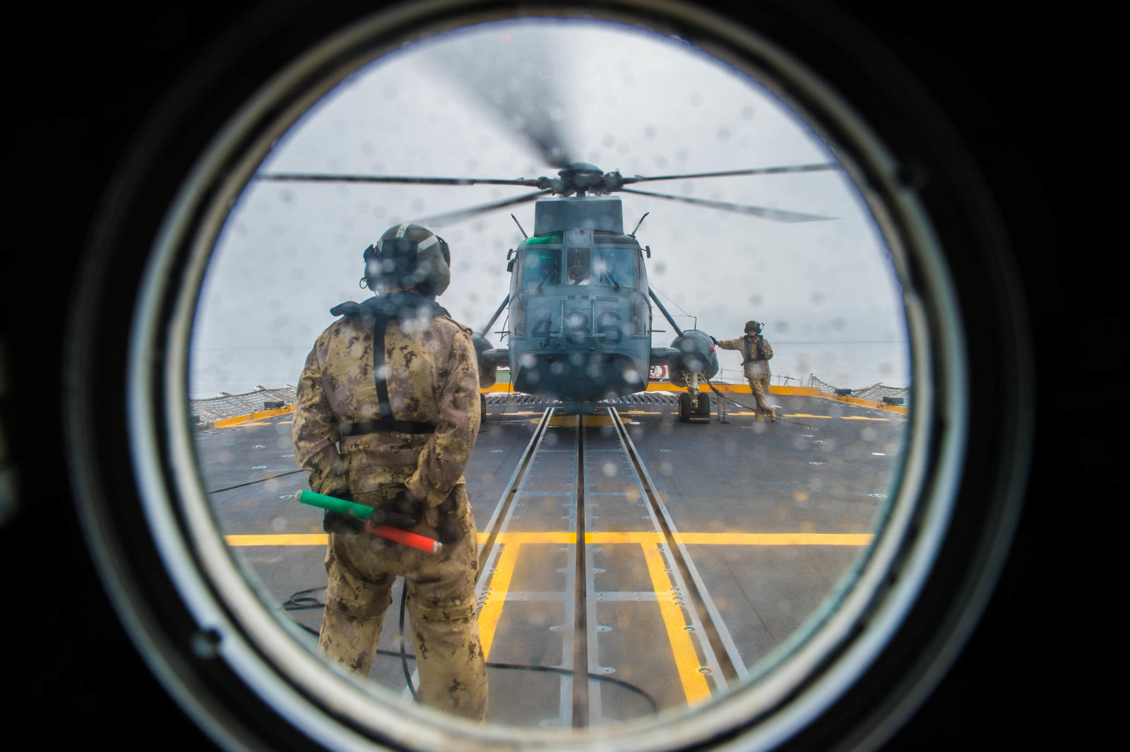 "An aviation technician from 443 Maritime Helicopter Squadron prepares to guide a Sea King helicopter attached to Her Majesty's Canadian Ship Winnipeg for flight training during Poseidon Cutlass on March 13, 2017. The new ""MNET"" online ""job translation"" tool is aimed at helping serving and former members of the Canadian Armed Forces transition to civilian life. PHOTO: Corporal Carbe Orellana, ET2017-4005-08"