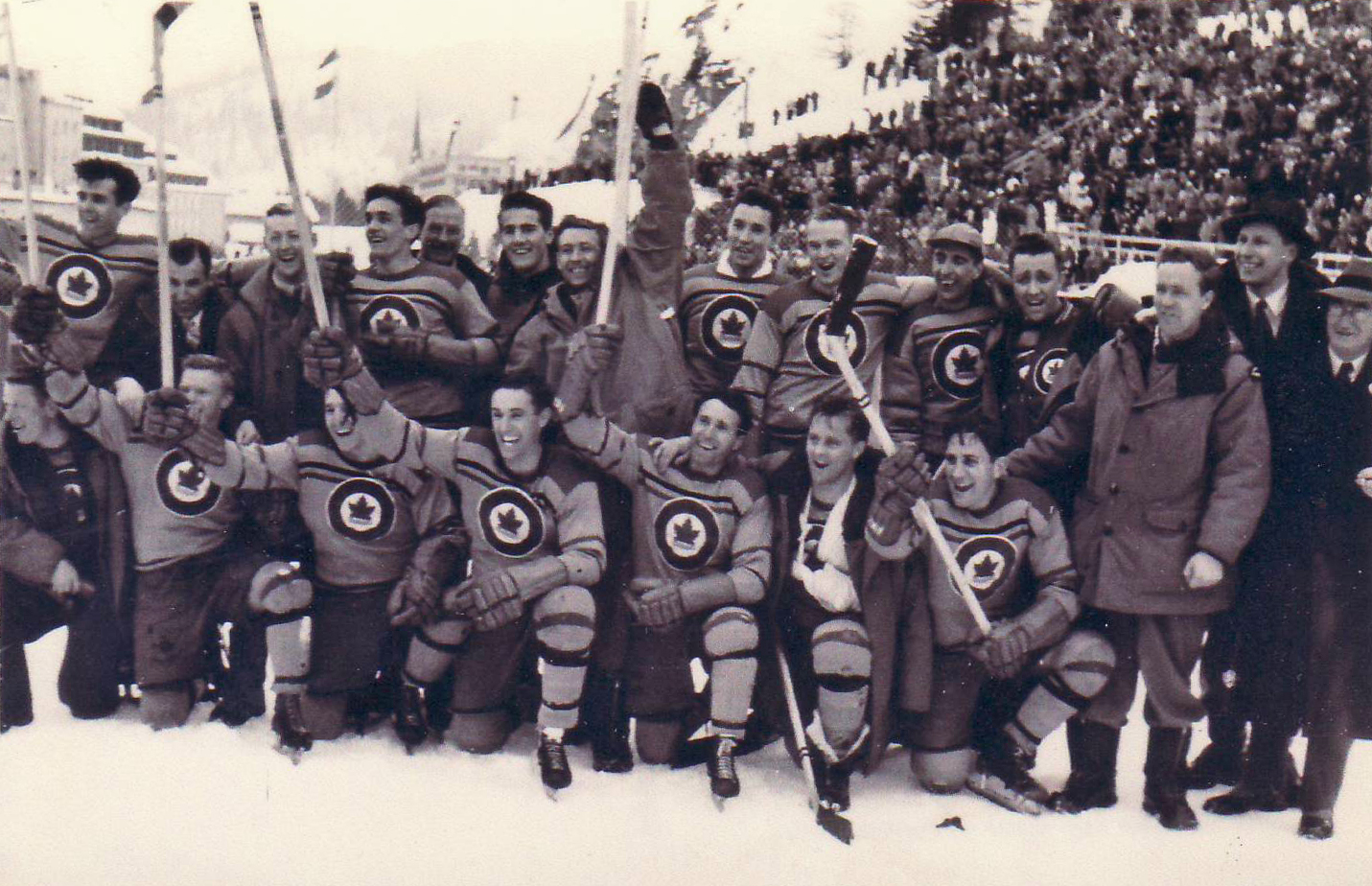 The RCAF Flyers celebrate their Gold Medal win over Switzerland on the outdoor rink at St. Moritz in 1948. Rear row (left to right): André LaPerrière, Hubert Brooks, Andy Gilpin, Ted Hibberd, A. Sydney Dawes, head of the Canadian Olympics Association, Pete Leichnitz, Irving Taylor, Wally Halder, George Mara, Murray Dowey, George McFaul, Frank Boucher, Sandy Watson, and George Dudley, head of the Canadian Amateur Hockey Association. Kneeling in front (left to right): Roy Forbes, Orville Gravelle, Reg Schroeter, Ab Renaud, Patsy Guzzo, Louis Lecompte and Frank Dunster.