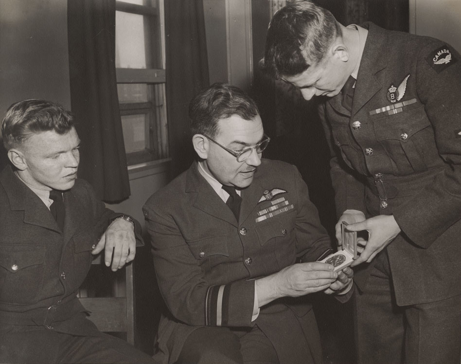 "The RCAF Flyers' Roy Forbes shows his Olympic ice hockey gold medal to Air Marshal Wilf Curtis, Chief of the Air Staff, on April 7, 1948, while Orval ""Red"" Gravelle looks on. Note bomber wing on Forbes' uniform. Air Marshal Curtis was a keen hockey fan and immediately supported the idea of sending an RCAF team to compete in the 1948 Winter Olympics. PHOTO: LAC MIKAN no. 4842101"