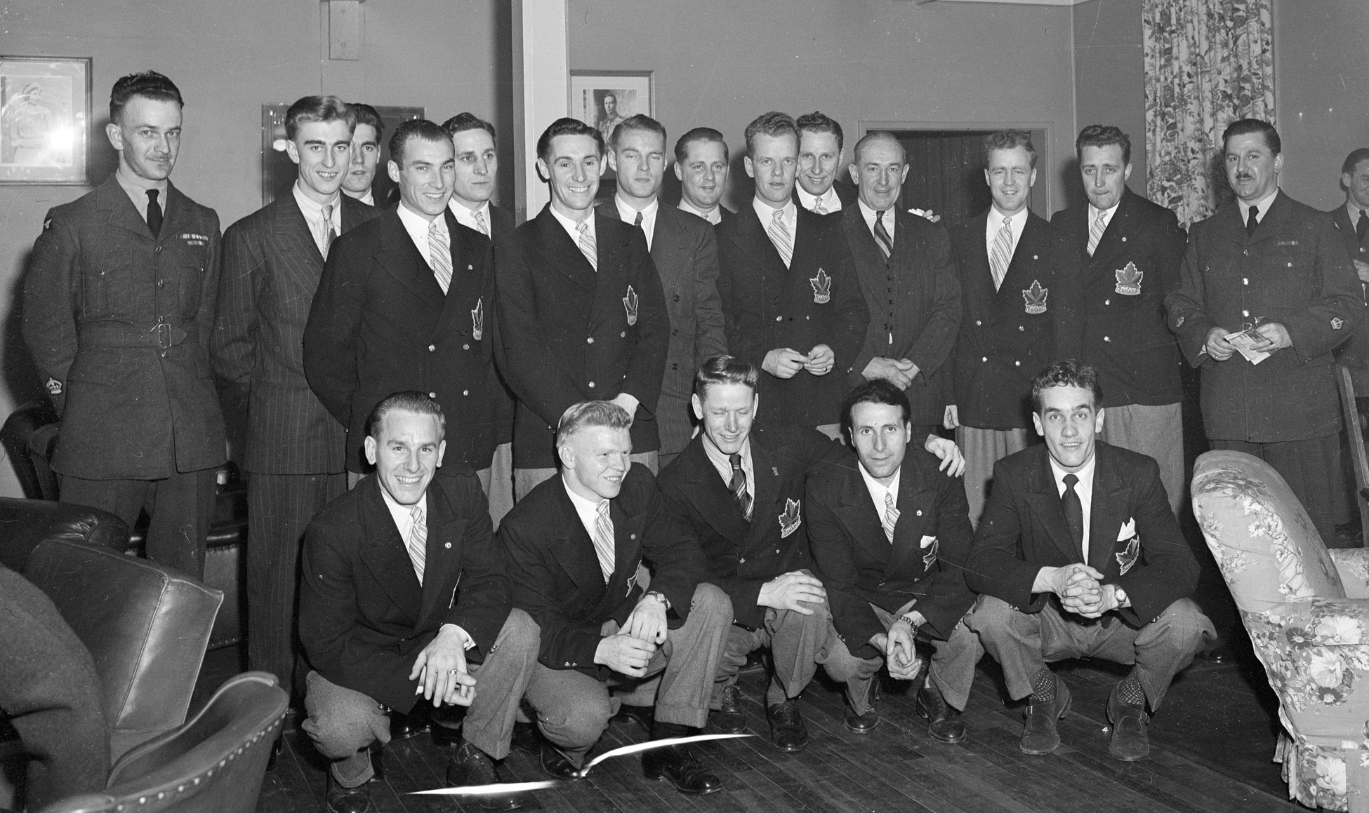 "The 1948 Olympic Champion RCAF Flyers gather for a photograph after receiving a tremendous ovation in the Sergeant's Mess at Ottawa's Beaver Barracks on April 8, 1948. Front row (left to right): Reg Schroeter, Orval Gravelle, Roy Forbes, Patsy Guzzo and Ted Hibberd. Back row (left to right): Warrant Officer Class 2 W.H. Fader, vice-president of the mess, Murray Dowey, Pete Lietchnitz, Hubert Brooks, Frank Dunster, Ab Renaud, George Mara, Louis LeCompte, Ross King, Sandy Watson, George ""Buck"" Boucher, Frank Boucher, Corporal George McFaul and Warrant Officer Class 2 Colin Campbell. Absent from the photo are André Laperrière and Wally Halder. George Boucher, Sergeant Frank Boucher's father, assisted in selecting the team, but could not be a member as he was a professional NHL player. PHOTO: DND Archives, PL-38853"