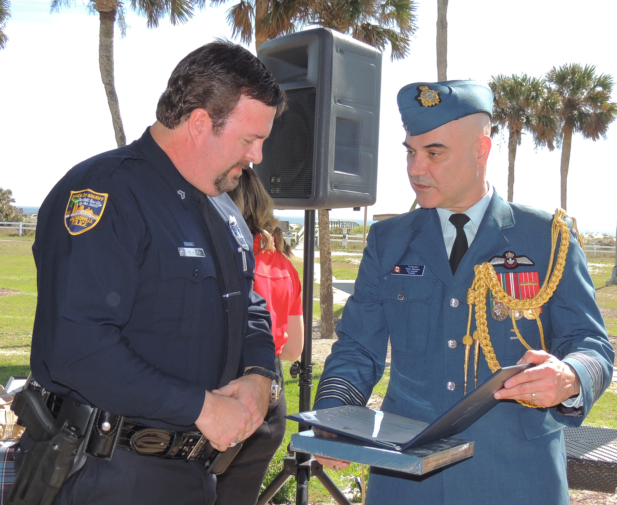 Colonel Tom Dunne (right), the Canadian air attaché at the Canadian Embassy in Washington, presents a letter of thanks signed by the commander of the Royal Canadian Air Force, Lieutenant-General Michael Hood, to Officer Nolan Kea of the Jacksonville Sheriff's Office. Officer Kea worked with Ranger Johnson to verify that the bundle of artifacts that Ranger Johnson discovered on the beach had belonged to Lieutenant Barry Troy. Officer Kea then notified the Embassy of Canada in Washington and held the items in secure storage until the transfer of the artifacts to the Royal Canadian Air Force, which occurred on February 26, 2018. PHOTO: Joanna Calder, RCAF public affairs