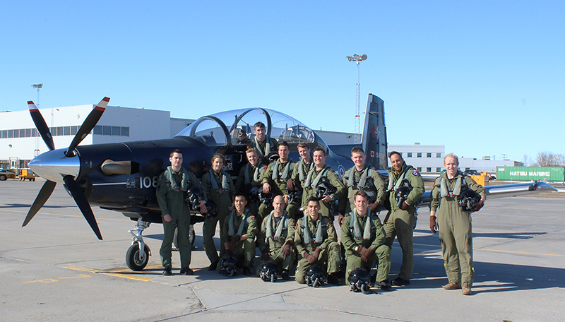 slide - Fourteen young people wearing olive green flight suits and holding helmets gather on and in front of the port wing of a small dark blue aircraft.