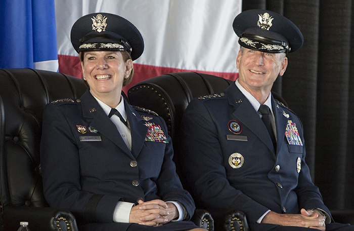 slide - A man and a woman, both wearing dark blue military uniforms, sit in leather wing-backed chairs on a stage with flags behind them.