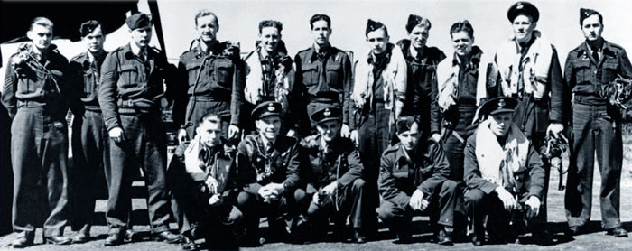 "This photo shows 16 of the 17 RCAF personnel who survived the Dambusters raid. Standing, left to right: Sergeant Steve Onancia, Sergeant Fred ""Doc"" Sutherland, Sergeant Harry O'Brien, Flight Sergeant Ken Brown, Flight Sergeant Harvey Weeks, Flight Sergeant John William ""Jack"" Thrasher, Pilot Officer George A. Deering, Sergeant William G. Radcliffe, Flight Sergeant Donald A. MacLean, Flight Lieutenant Joseph C. McCarthy and Flight Sergeant Grant S. MacDonald, air gunner, F-Freddie. Kneeling, left to right: Warrant Percy E. Pigeon, Flying Officer Harlo T. Taerum, Flying Officer Danny R. ""Revie"" Walker, Sergeant Chester B. Gowrie, and Flying Officer David Rodger, air gunner on T-Tommy. A 17th RCAF airman, Pilot Officer John Fraser, was shot down at the Möhne Dam and parachuted to safety to become a prisoner of war. PHOTO: Bomber Command Museum of Canada"